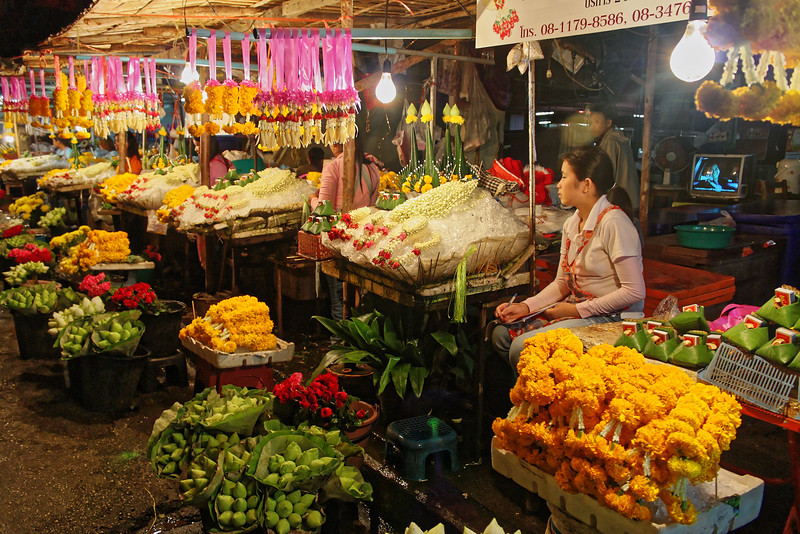 Flower sellers at Warorot Market with their fragrant and colorful offerings. Flowers and floral arrangements are an important part of everyday Thai social and religious life. The garlands hanging on pink ribbons in the photo are <i>malai.</i> Fashioned from marigold blossoms or jasmine buds, they are used in a variety of ways, including as offerings at shrines or, hung from a car's rearview mirror, as protection against accidents.