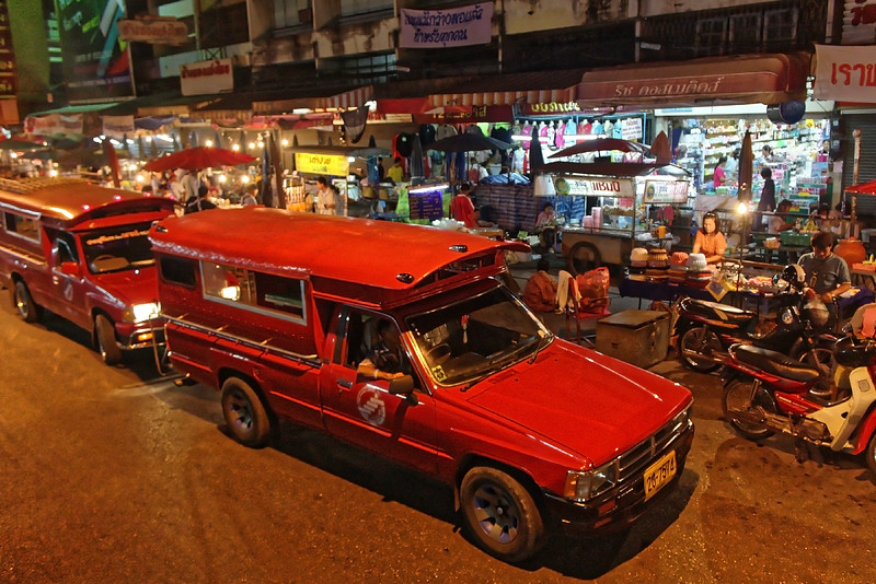 A popular means of transportation around the city are the <i>songthaew,</i> pickup trucks converted to carry passengers on benches that line either side in back.