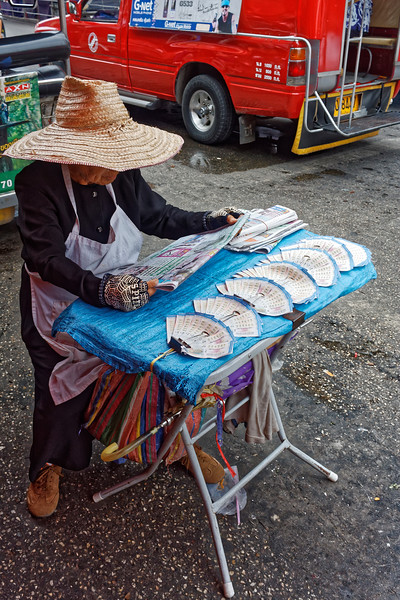 Lottery-ticket seller, who has set up shop right <i>in</i> the street, studies her morning paper.