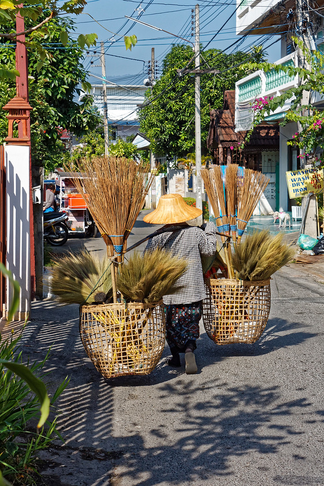 A diminutive broom-seller peddles her handmade wares along streets in the old walled section of Chiang Mai
