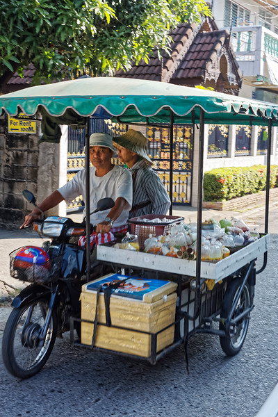 On a lane off of Moon Muang Road, a couple zipping along on their way to a spot where they will sell the packages of food prepared earlier