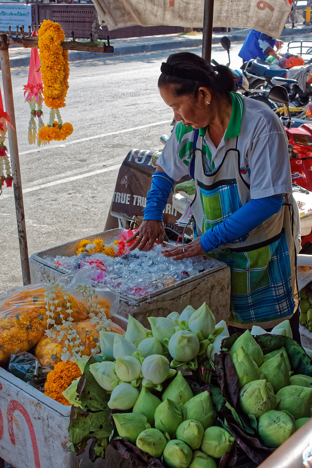 Woman selling marigold garlands and white-lotus buds, both used for merit-making