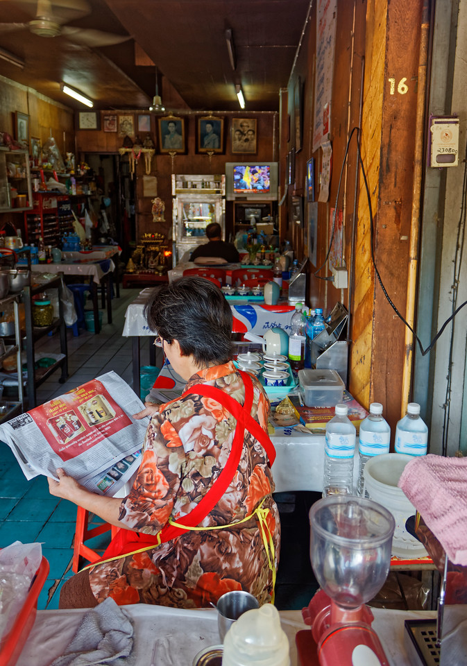 The proprietress of a streetside shophouse restaurant peruses her morning paper.