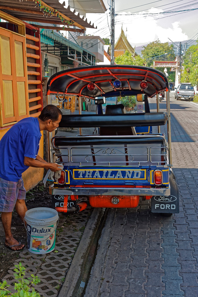 A <i>tuk-tuk</i> driver polishing his vehicle