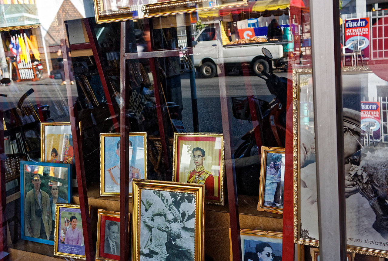 Reflections in the window of a frame shop with images of King Rama IX and the queen
