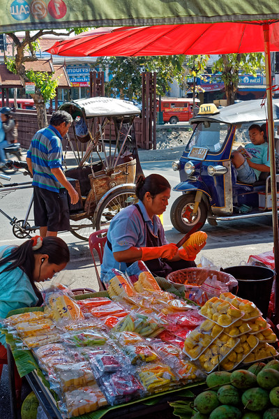 More fruit sellers on Moon Muang Road. If you look carefully you can also see, just barely, four modes of local transportation: motorcycle/motorbike (fleeing off to the left); <i>samlor,</i> a three-wheeled carriage propelled like a bicycle; <i>tuk-tuk</i> (at right); and, in the background, a red <i>songthaew,</i> essentially a pickup truck converted to carry passengers in back.