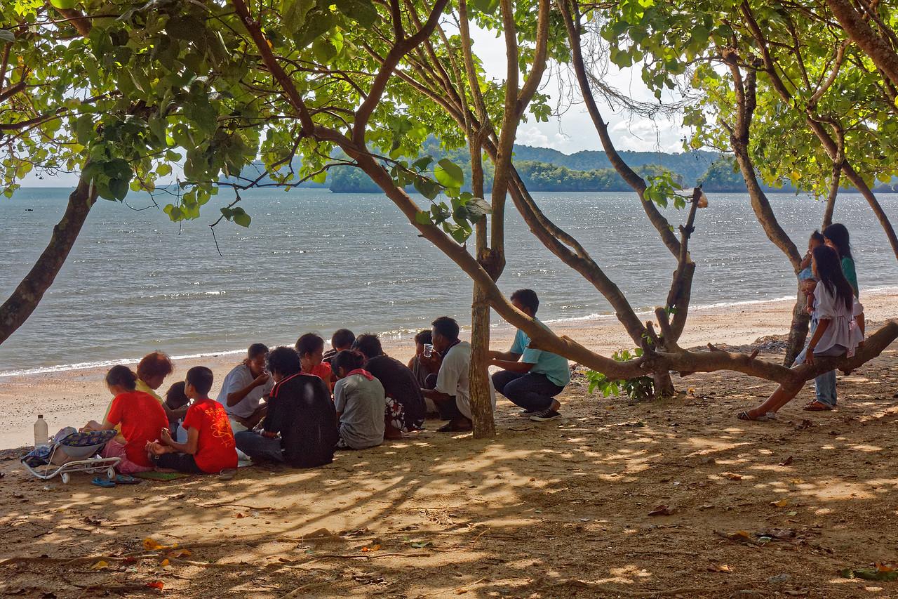 Family picnic on the shore of the Andaman Sea and the beach at Ao Nang