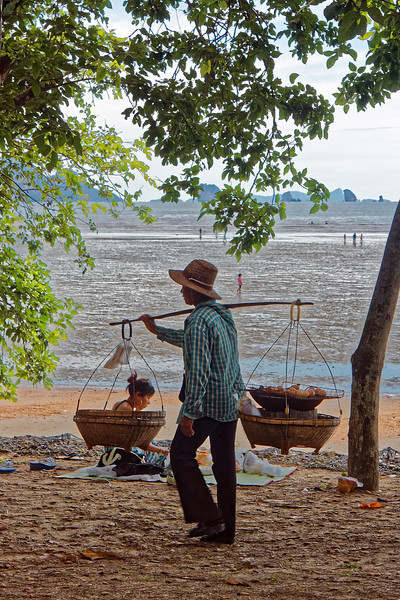 "A peddler of what the Thais call ""roasted"" eggs carries his wares on his shoulder as he traverses Nopparat Thara Beach at Ao Nang, southern Thailand. The boiled eggs are kept warm by the charcoal burner under the wire rack they're on."