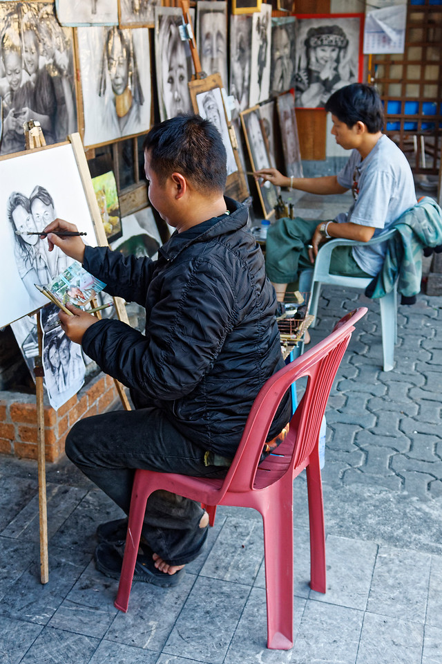 Portrait sketch artists on a street in Chiang Mai. They work from photos or from  live subjects.