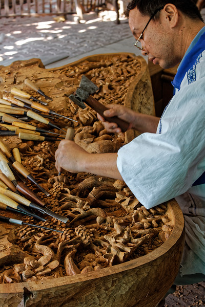 Wood carver at work on another intricate scene, near Bangkok