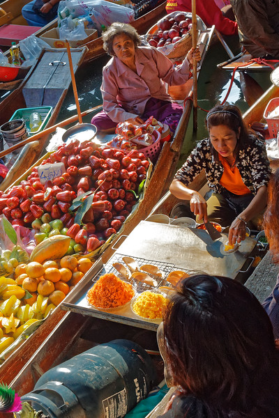 A boat filled with star fruit, oranges, papaya, and rose apples. The woman on the right is preparing <i>khanom bueng,</i> Thai  crepes or crispy pancakes. They're usually made with mungbean or rice flour, eggs, and coconut cream, with toppings of salty shredded shrimp or sweet shredded coconut.