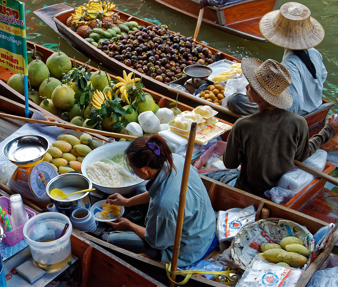 Preparing sticky rice with mango alongside boats offering pomelo, coconuts, bananas, pineapples, mangosteen, and other goodies