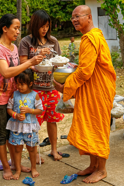 Giving the monks offerings of food, flowers, or other necessities provides the faithful with an opportunity to make merit, and is so considered. Out of respect, followers remove their footwear, as the monks themselves are barefoot on their morning rounds.