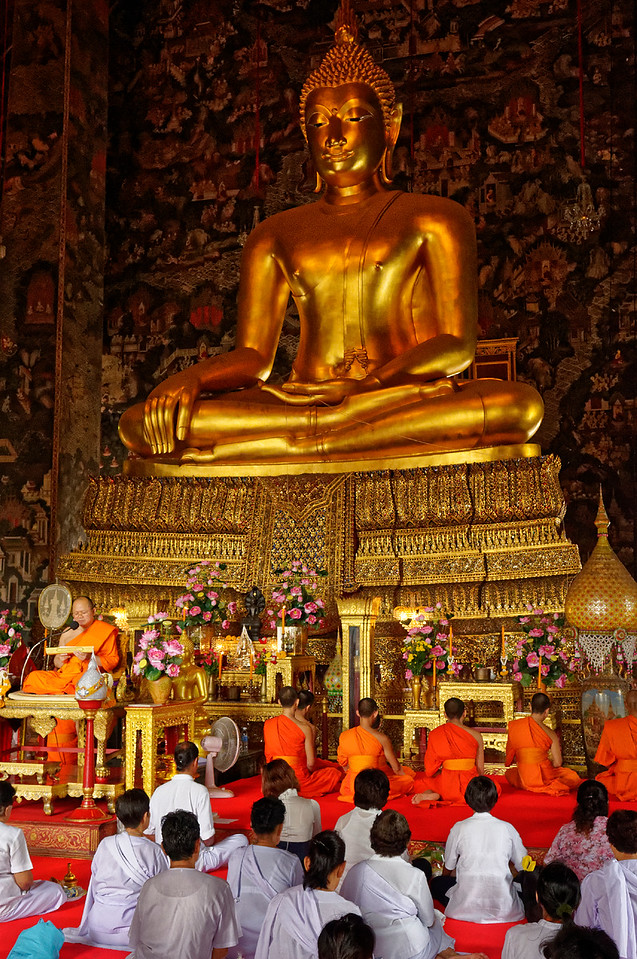 Congregants and monks before the magnificent 14th-century Sri Sakyamuni Buddha at Wat Suthat, Bangkok. Rama I brought this Buddha from its original home in Sukhothai, ordering that the temple be built in part to house this image in his new capital at Bangkok.