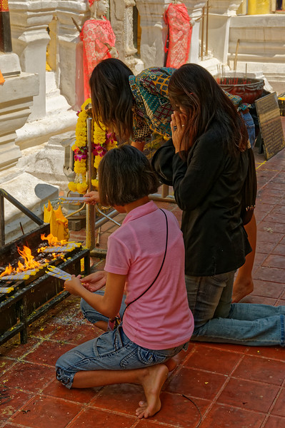 More merit-making, here with candles and garlands of flowers. Wat Phra That Lampang Luang, in Lampang, northern Thailand