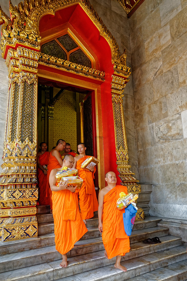 Monks emerging from the ordination ceremony with merit-making gifts