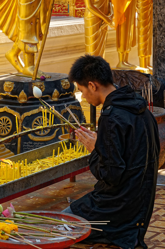 Making merit with lotus-bud and incense offerings at Wat Phra Boromathat Doi Suthep, Chiang Mai, a temple whose origins date to the late 14th century