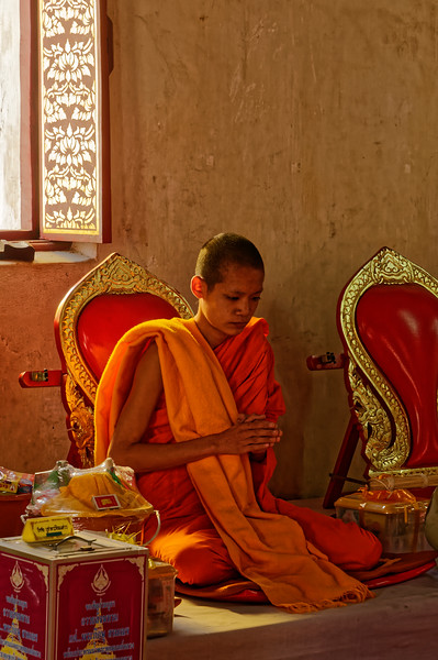 A young monk giving blessings to followers who have just made donations to the temple. Wat Phra That Chae Haeng, in Nan, in the north of Thailand