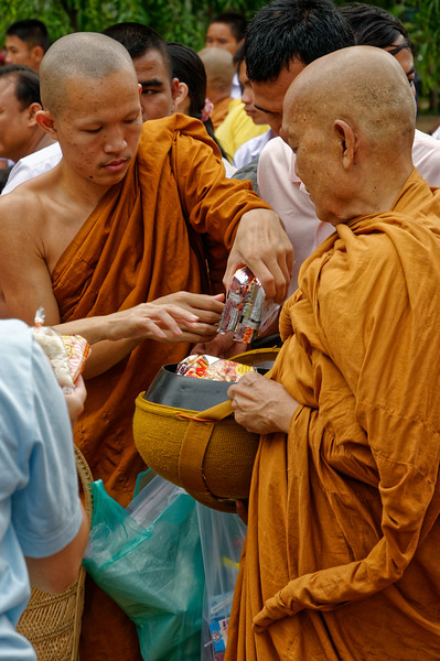 The abbot of Wat Luang in Sisaket receiving offerings passed along to him by one of the monks from the temple