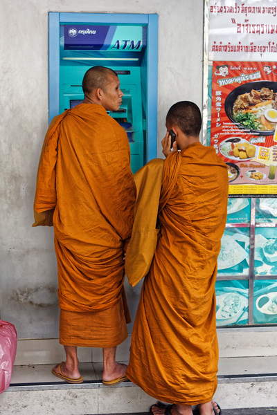 Monks at an ATM in Bangkok, cell phone to one ear