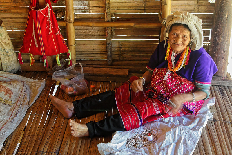 Karen woman stringing seeds to be used for clothing decoration