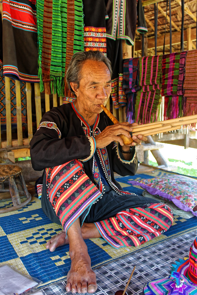 Yellow Lahu man playing a musical instrument