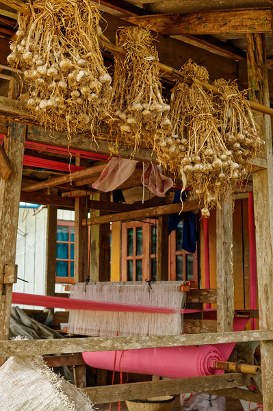 Garlic and a loom on the porch of a home in Ban La Up