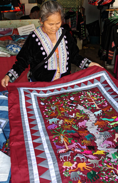"A Hmong woman displays a vibrantly colored ""story cloth."" Such cloths typically depict narrative scenes from Hmong history and folklore and, though of relatively recent development, may be considered part of a larger tradition of Hmong embroidered textiles dating back to their early origins in China."