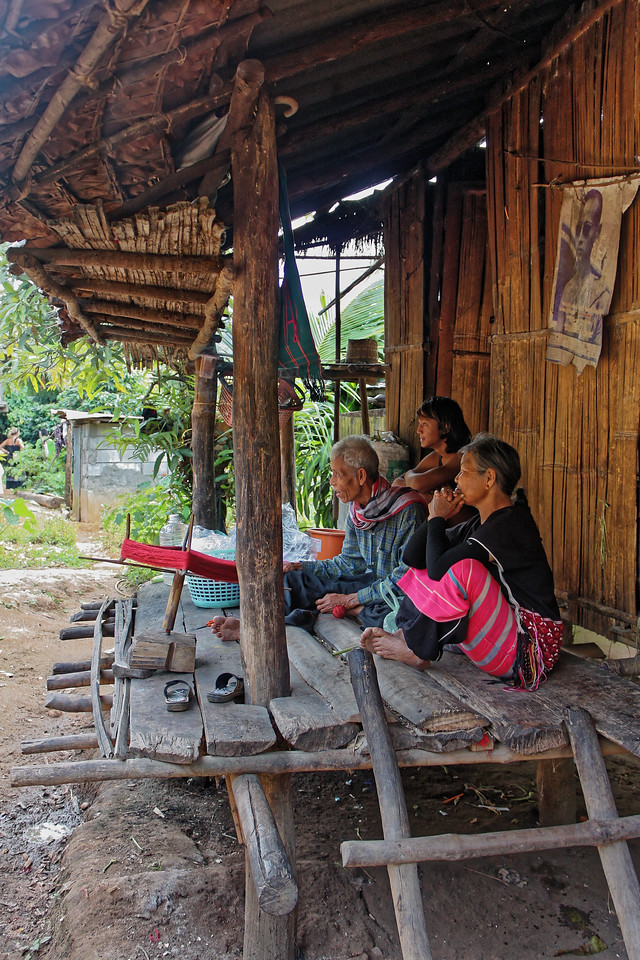 Karen hill tribe people at home in their northern village. The photo on the wall is of king Rama IX as a young man.
