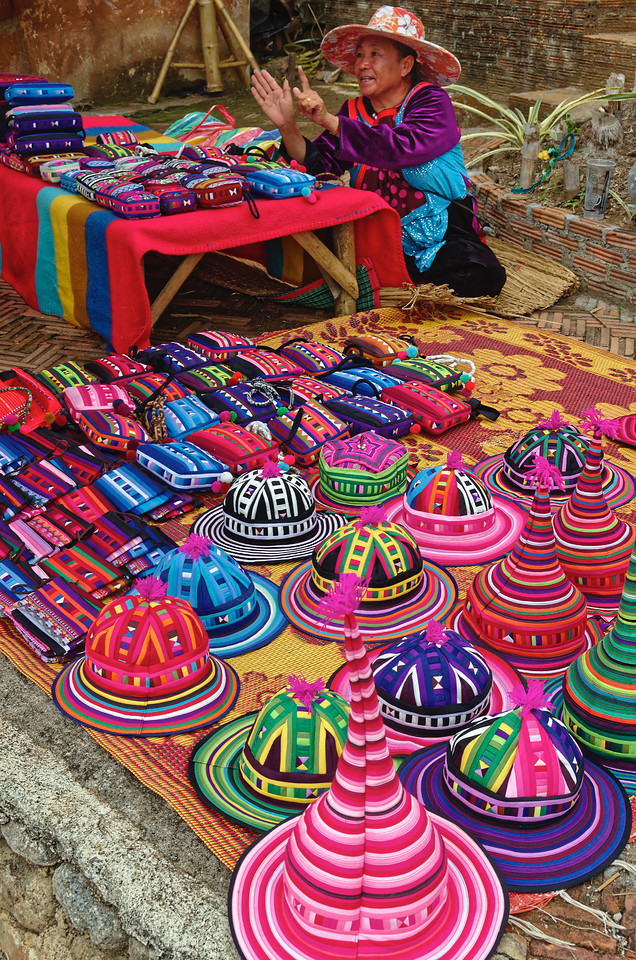 Woman selling hill tribe hats and bags at Santichon, near Pai, northern Thailand