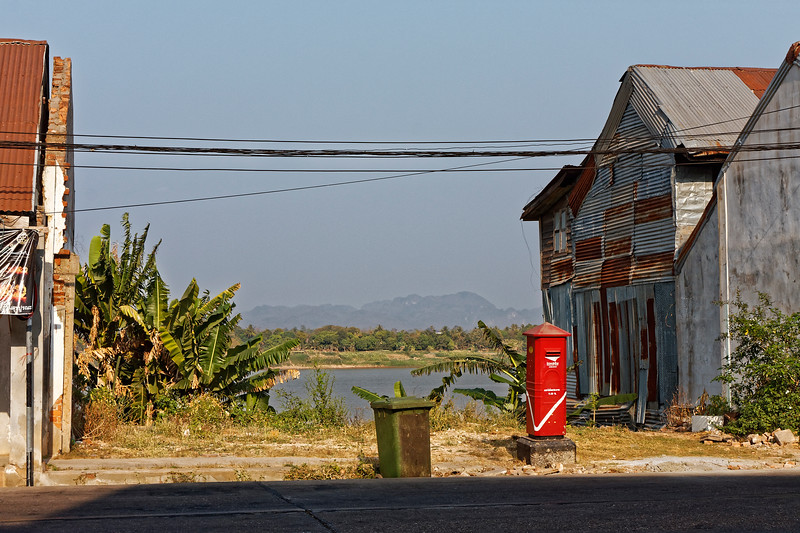 A glimpse of the Mekong and Laos from a Nakhon Phanom street with mailbox