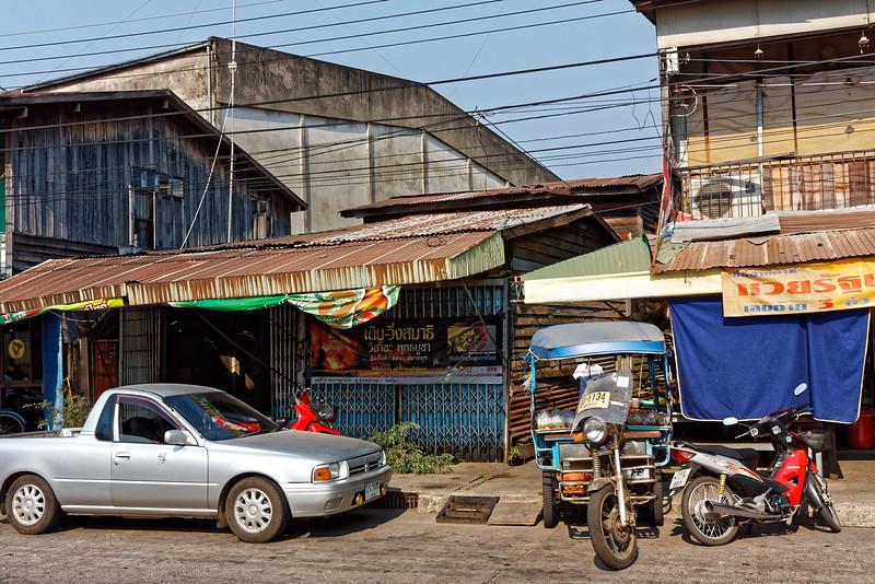 Street scene with pickup truck, <i>tuk-tuk,</i> motorbikes. Nakhon Phanom
