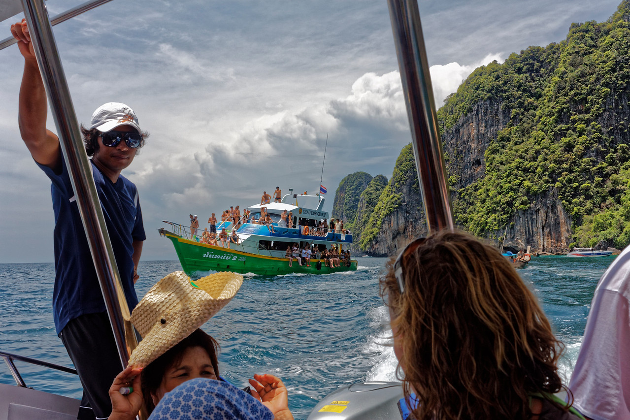 View from a speedboat to a tourist-filled ferry and to some of the limestone cliffs that line the Andaman Sea coast, southern Thailand