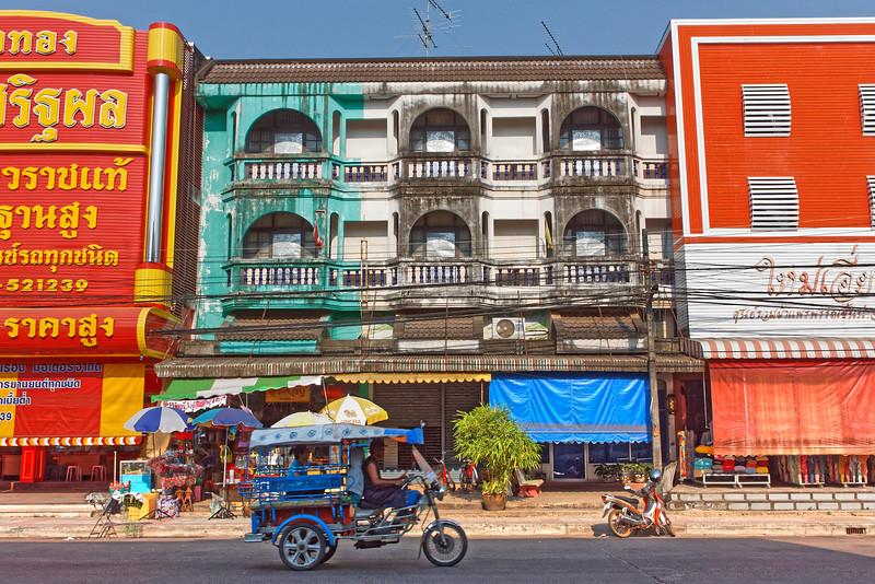 <i>Tuk-tuk</i> with passenger zipping along a downtown street, Nakhon Phanom