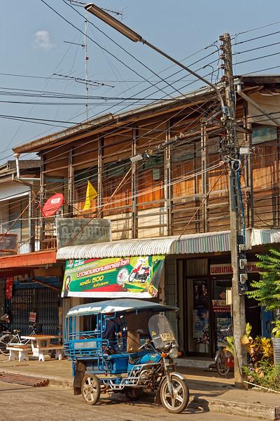 Vintage <i>tuk-tuk,</i> overhead wires, antenna, shophouses, Nakhon Phanom