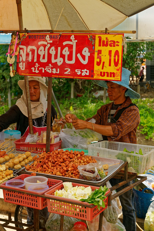 In the village of Rasi Salai, Sisaket Province, a couple selling meatballs made with fish, pork, or beef—as well as sausages—the latter known as 'Thai hot dogs'