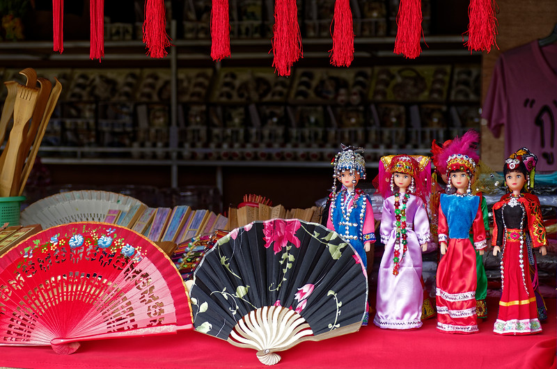 Hill tribe dolls and Chinese-style fans in a shop window at Santichon, near Pai, Chiang Mai Province