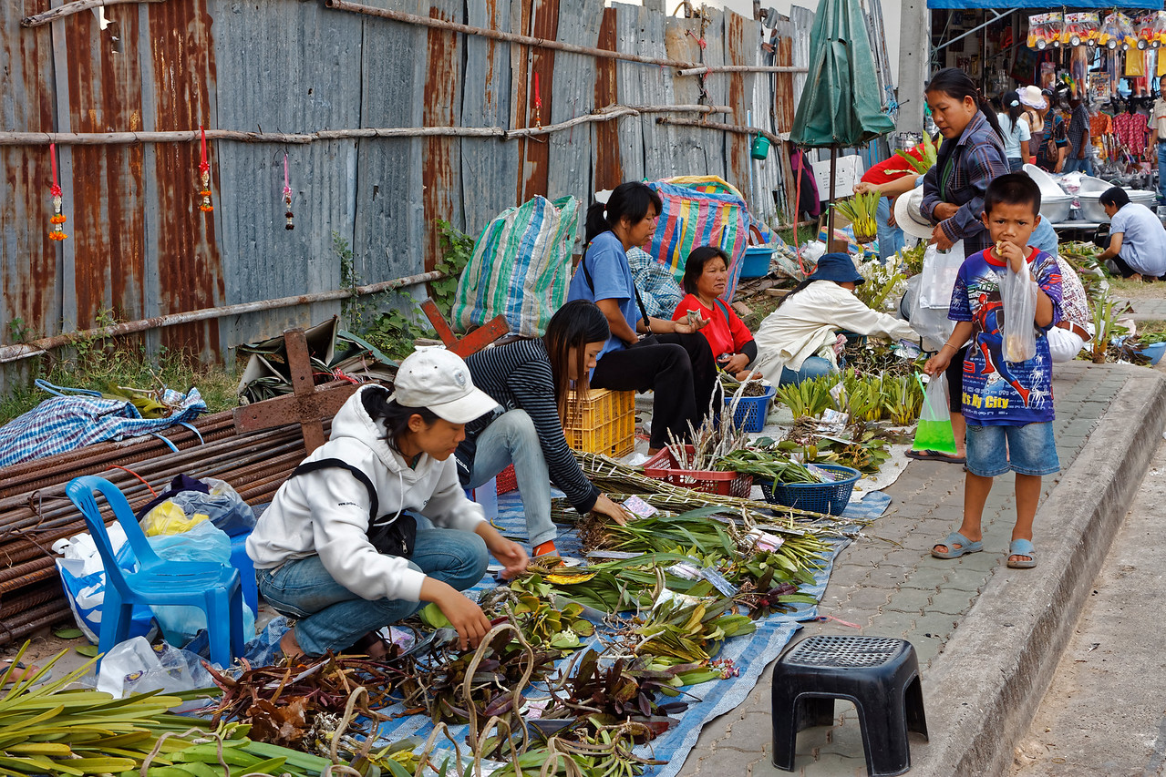 Orchid sellers setting up shop along the sidewalk at Mukdahan, northeast Thailand
