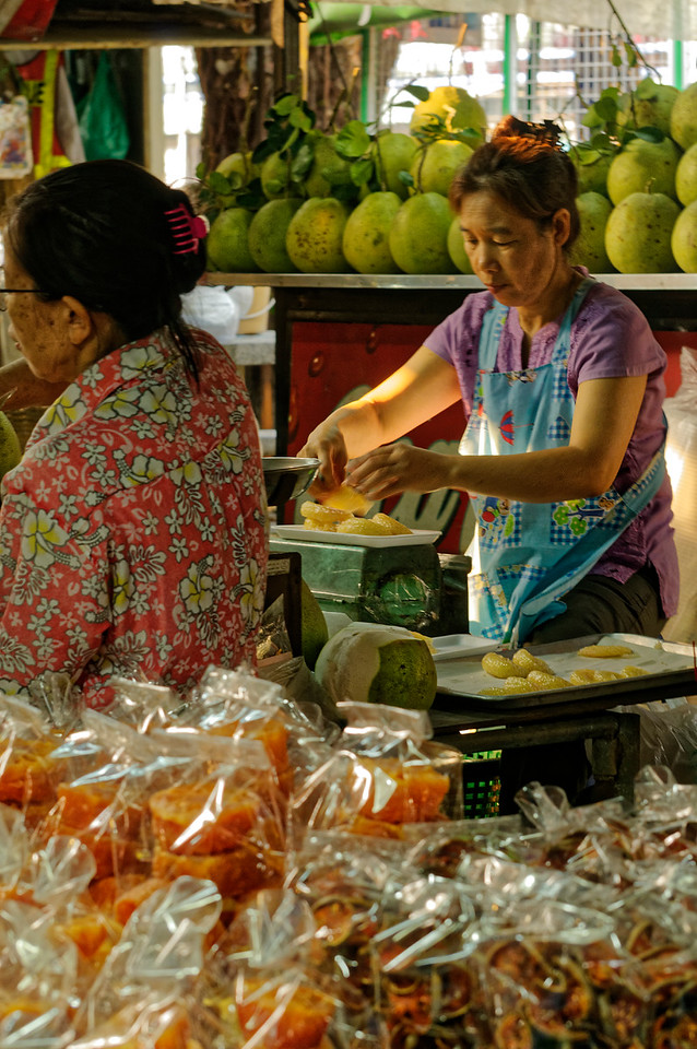 Woman separating and bagging pomelo sections at Don Wai Market