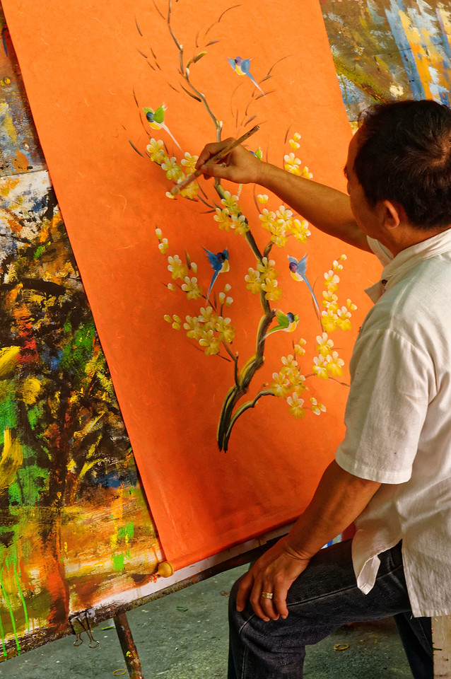 Artists at Bo Sang paint designs on hanging scrolls and hand-held fans as well the umbrellas.