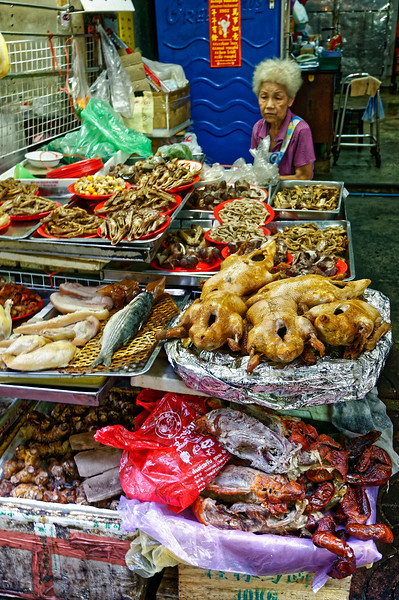 Fresh fish, duck, ducks' bills, chicken, and pork are among the items offered by this lady.