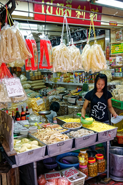 An offering of dried fish maw in the plastic bags hanging overhead along with a variety of other foodstuffs. The smallish yellow morsels that the woman is scooping into a bowl are gingko seeds, from the gingko biloba tree. One way they are eaten is in congee, a rice porridge, called <i>jōk</i> in Thai.