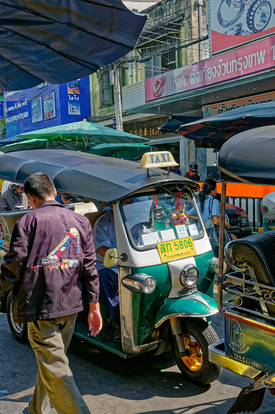 Alleyway jammed with <i>tuk-tuks</i> and shoppers on foot