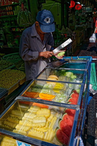 Slicing green mango over a case with fresh pineapple, watermelon, and cantaloupe