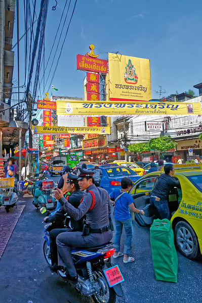 Street scene with two-man police motorbike, a common sight in Thailand
