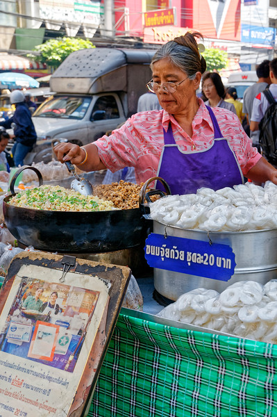 This woman is making <i>jui guai,</i> a Chinatown specialty made from fried minced garlic and chopped preserved turnips or radishes, with ground pork optional, all seasoned with a thick soy sauce or fish sauce.This topping is placed on the white cakes seen on the right, which are made from rice flour.