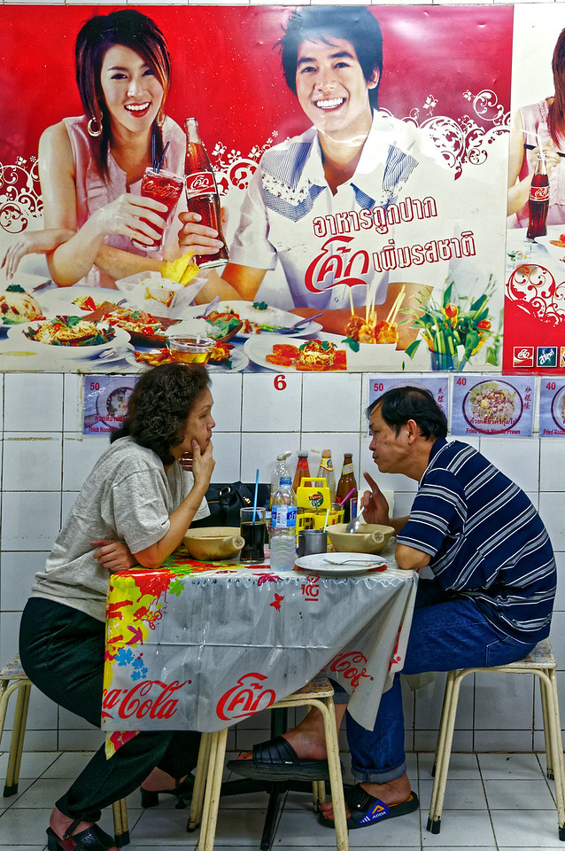 A smiling couple sharing a bottle of the ubiquitous Coca-Cola hovers over a pair of diners in a hole-in-the-wall Chinatown restaurant.