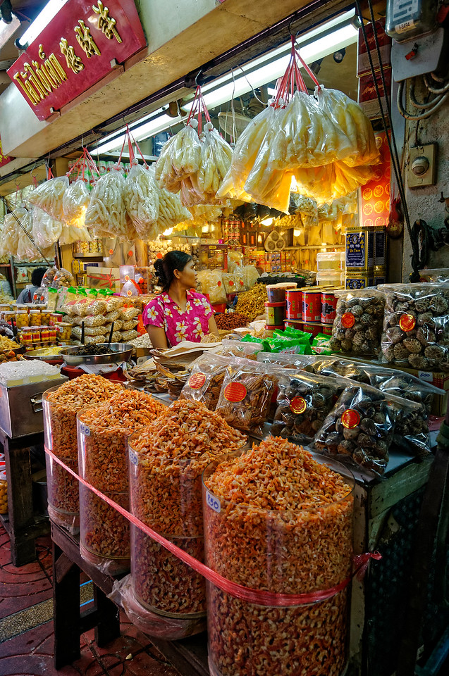 Visitors to the indoor markets in Bangkok's Chinatown are confronted with an almost bewildering warren of individual merchandisers whose overflowing displays line narrow aisles that swarm with heavy customer traffic. The woman in this photo is selling dried shrimp, squid, mushrooms, and other items.