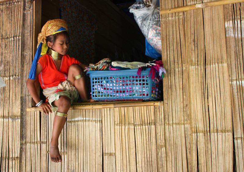 A young Paduang girl helping fold laundry