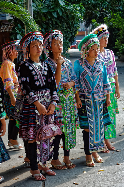 Hmong girls in their elaborately embroidered finery and fancy, tasseled hats